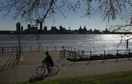 A man passes the skyline of Liverpool as he cycles along the banks of the River Mersey in Seacombe northern England April 18 , 2015. REUTERS/Phil Noble