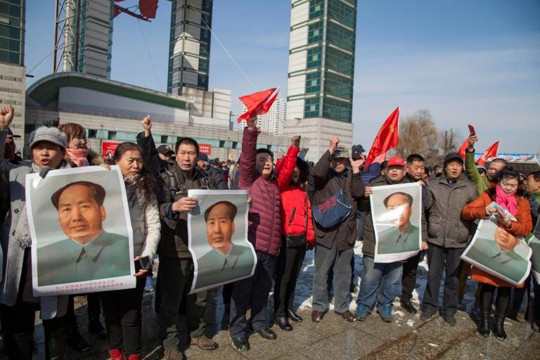 Chinese activists hold posters of Mao Zedong during a protest calling for a boycott of South Korean goods in Jilin, on March 5, 2017