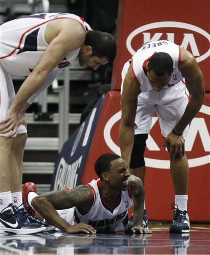 Atlanta Hawks guard Jeff Teague, bottom, is helped to his feet by teammates Tracy McGrady, right, and Vladimir Radmanovic (77) during the second quarter of an NBA basketball game Wednesday, Feb. 8, 2012, in Atlanta. (AP Photo/John Bazemore)