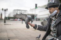 Belhussein Abdelsalam, 58, a Charlie Chaplin impersonator feeds pigeons as he waits for customers in one of the main avenues in Rabat, Morocco, Wednesday, Dec. 16, 2020. When 58-year-old Moroccan Belhussein Abdelsalam was arrested and lost his job three decades ago, he saw Charlie Chaplin on television and in that moment decided upon a new career: impersonating the British actor and silent movie maker remembered for his Little Tramp character. (AP Photo/Mosa'ab Elshamy)