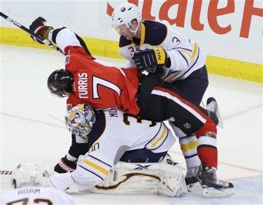 Ottawa Senators' Kyle Turris (7) falls on top of Buffalo Sabres goaltender Ryan Miller (30) after being checked by Sabres' Jordan Leopold (3) during the second period of an NHL hockey game in Ottawa, Ontario, Tuesday, Dec. 20, 2011. (AP Photo/The Canadian Press, Fred Chartrand)