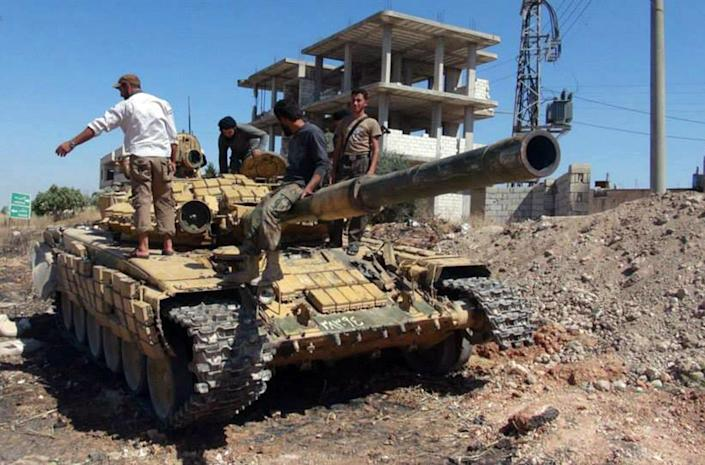 In this Friday, June 14, 2013 citizen journalism image provided by Edlib News Network, ENN, Syrian rebels stand on top of a tank they took after storming the Iskan military base in Idlib province, northern Syria. After weeks of fighting the rebels captured tanks as well as other vehicles and artillery in the area. (AP Photo/Edlib News Network ENN) THE ASSOCIATED PRESS IS UNABLE TO INDEPENDENTLY VERIFY THE AUTHENTICITY, CONTENT, LOCATION OR DATE OF THIS HANDOUT PHOTO