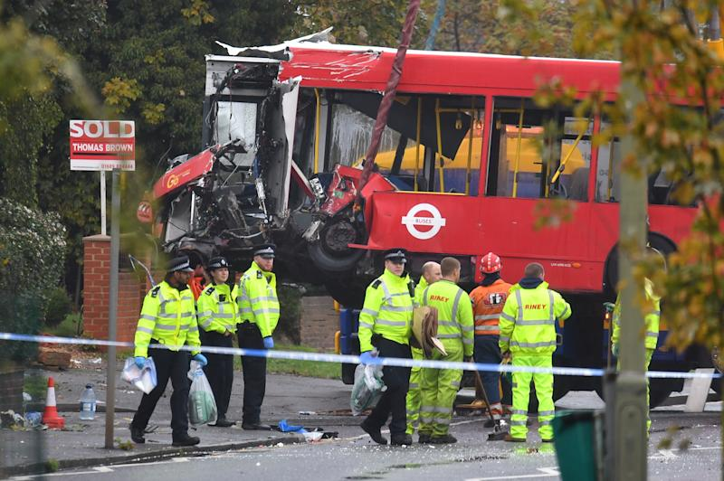 Police and recovery workers remove a damaged bus from the scene of a crash in Sevenoaks Road, Orpington, south-east London, where a man has been arrested on suspicion of causing death by dangerous driving after a crash in which a person died and 15 others were injured.