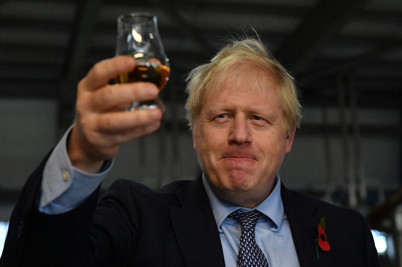 Britain's Prime Minister Boris Johnson tastes whisky during a general election campaign visit (AP)