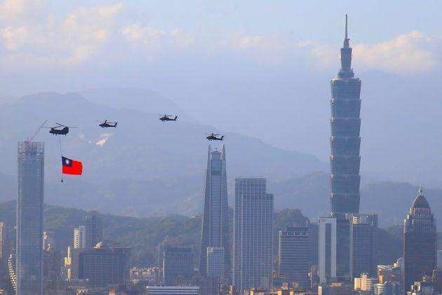 A military helicopter carrying a tremendous Taiwan flag flies over near  Taipei 101, as part of the rehearsal ahead of the Double-tenth national day celebration, amid China's growing military threats, in New Taipei, Taiwan, 5 October 2021. China has been sending record number of warplanes to the ADIZ of the self ruled island, whilst Taiwan has been building better relations with the US, Australia, Japan, and other European countries including Lithuania, Poland, Czech Republic. (Photo by Ceng Shou Yi/NurPhoto via Getty Images) (Photo: NurPhoto via Getty Images)