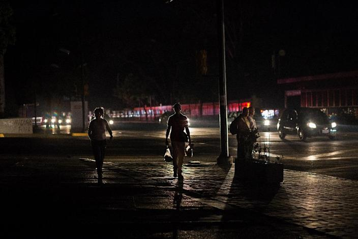 People walk along a dark street during a power outage in Caracas, on March 30, 2019 (AFP Photo/CRISTIAN HERNANDEZ)
