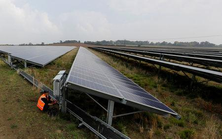 Anesco engineer Tommy Good works on Clayhill Solar Power Farm, Britain's first to operate without a government subsidy in Westoning, Britain September 26, 2017. REUTERS/Darren Staples