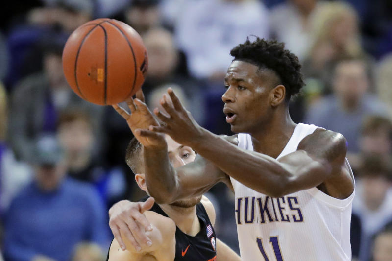 Washington guard Nahziah Carter, right, passes the ball against the defense of Oregon State forward Tres Tinkle, left, during the first half of an NCAA college basketball game Thursday, Jan. 16, 2020, in Seattle. (AP Photo/Ted S. Warren)