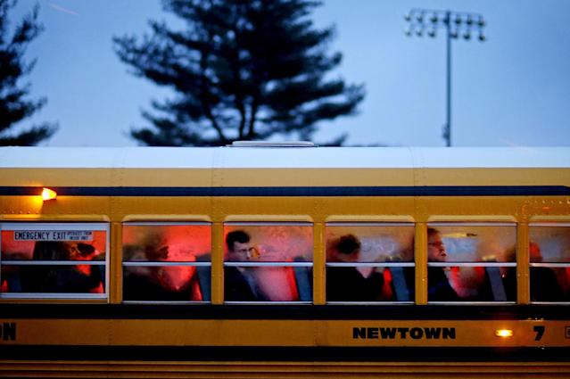 <p>People arrive on a school bus at Newtown High School for a memorial vigil attended by President Barack Obama for the victims of the Sandy Hook Elementary School shooting, Dec. 16, 2012, in Newtown, Conn. (AP Photo/David Goldman) </p>
