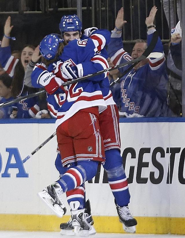 New York Rangers left wing Carl Hagelin (62) and New York Rangers center Brian Boyle hug after Hagelin scored during the first period of Game 4 of the NHL hockey Stanley Cup playoffs Eastern Conference finals against the Montreal Canadiens, Sunday, May 25, 2014, in New York. (AP Photo/Kathy Willens)