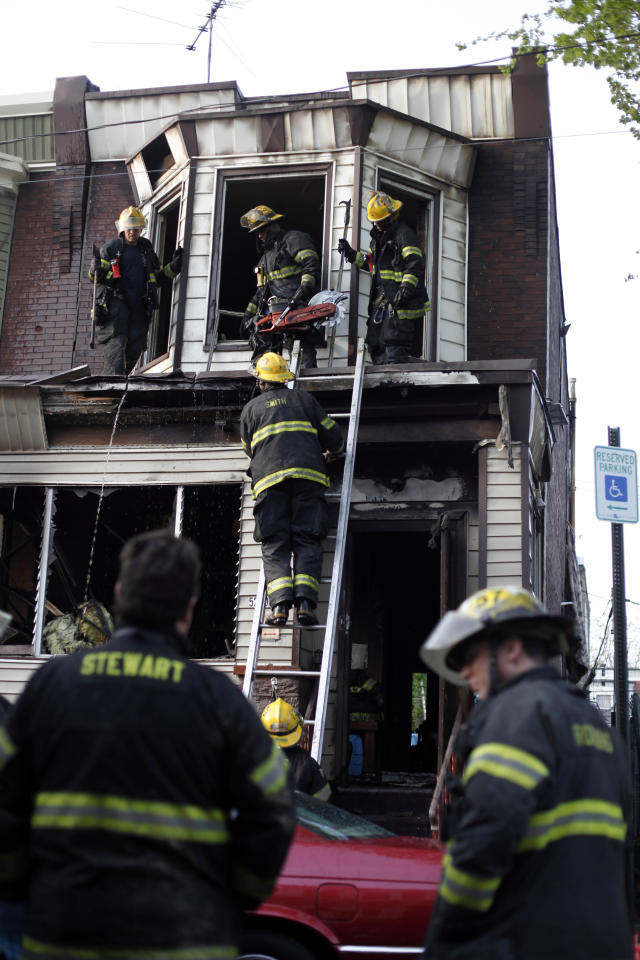 Firefighters work the scene of a deadly row home fire Monday, April 16, 2012, in Philadelphia. Officials say the early morning house fire has claimed the lives of four people in Philadelphia, including two children. (AP Photo/Matt Rourke)