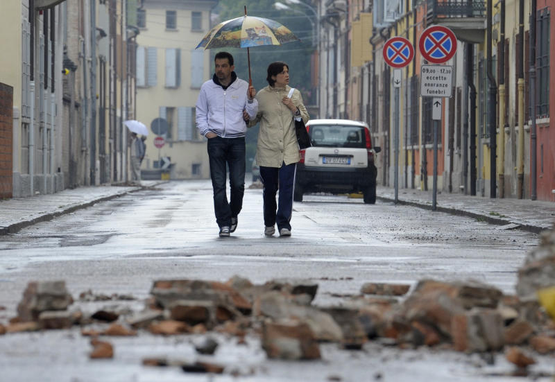 Residents view damage caused by a magnitude-6.0 temblor in Finale Emilia northern Italy, Sunday, May 20, 2012. One of the worst quakes to hit northeast Italy in hundreds of years rattled the region around Bologna early Sunday, killing at least four people, collapsing factories and sending residents running out into the streets, emergency services said. (AP Photo/Marco Vasini)