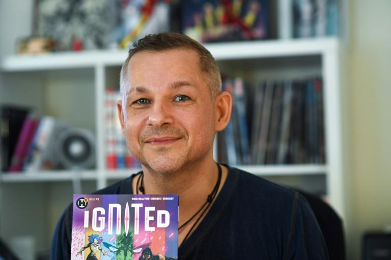 """French comic book illustrator Phil Briones displays his comic book """"Ignited,"""" which tackles the politically controversial topic of mass shootings head-on, in his home office in Los Angeles (AFP Photo/Robyn Beck)"""