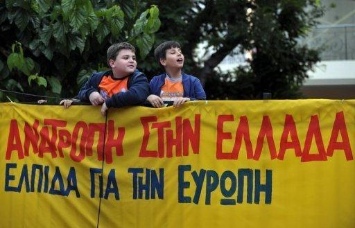 Greek children watch the Syriza party leader (unseen) make a speech in Athens in May 2012. No debt repayments, higher salaries and freedom from EU-IMF tutelage: Greece under the radical leftists, who are poised to win a June 17 election, seems a world removed from its current recession nightmare