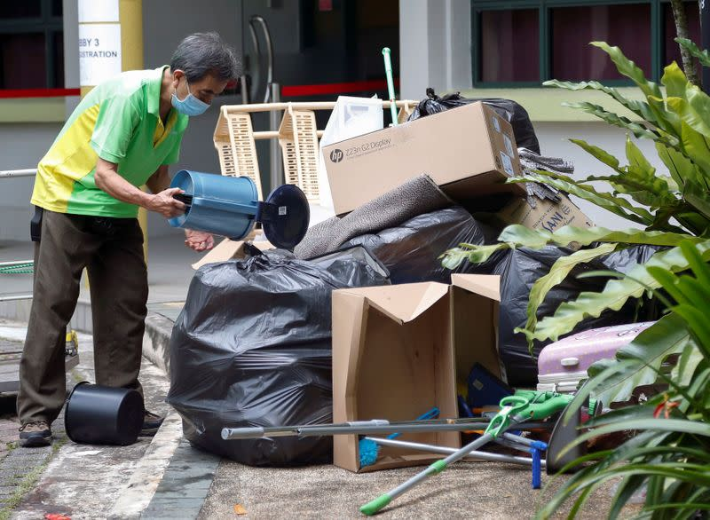 A worker clears rubbish in a dormitory area that is being used as a quarantine zone within Nanyang Technological University in Singapore