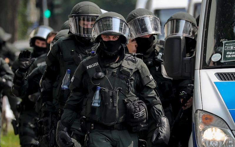 German riot police walk next to a police vehicle during a rally outside Schlump station - Credit: EPA/ARMANDO BABANI