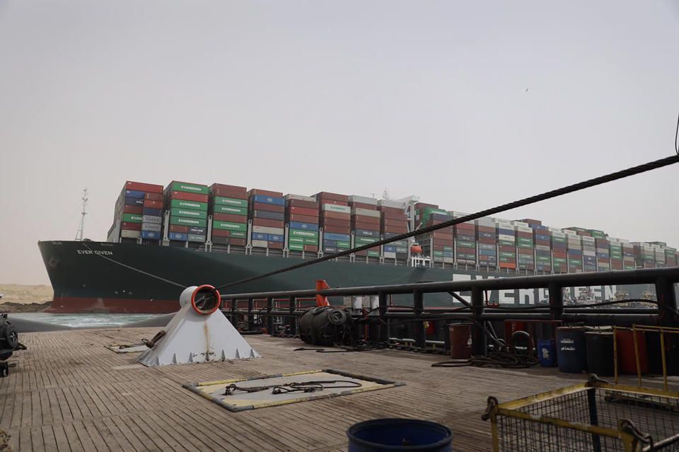 This photo released by the Suez Canal Authority on Thursday, March 25, 2021, shows the Ever Given, a Panama-flagged cargo ship, after it become wedged across the Suez Canal and blocking traffic in the vital waterway from another vessel. An operation is underway to try to work free the ship, which further imperiled global shipping Thursday as at least 150 other vessels needing to pass through the crucial waterway idled waiting for the obstruction to clear. (Suez Canal Authority via AP)