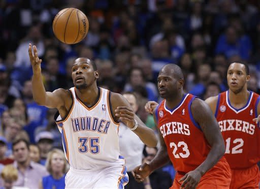 Oklahoma City Thunder forward Kevin Durant (35) reaches for the ball in front of Philadelphia 76ers guard Jason Richardson (23) and forward Evan Turner (12) in the second quarter of an NBA basketball game in Oklahoma City, Friday, Jan. 4, 2013. (AP Photo/Sue Ogrocki)
