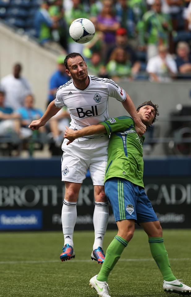SEATTLE, WA - AUGUST 18:  Andy O'Brien #40 of the Vancouver Whitecaps heads the ball against Jeff Parke #31 of the Seattle Sounders FC at CenturyLink Field on August 18, 2012 in Seattle, Washington.  (Photo by Otto Greule Jr/Getty Images)