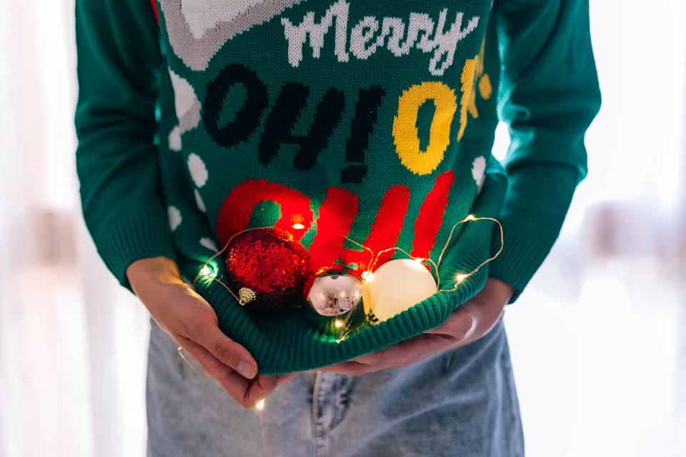 Unrecognizable woman holding Christmas tree balls in a Christmas jumper with lights