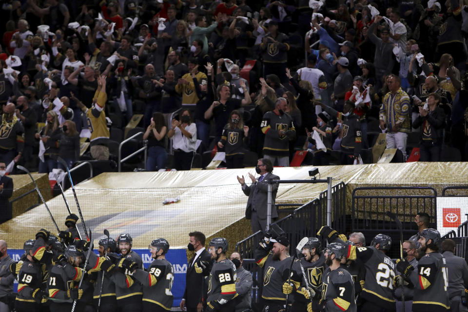 The Vegas Golden Knights bench celebrates the team's final goal against the Minnesota Wild during the third period of Game 7 of an NHL hockey Stanley Cup first-round playoff series Friday, May 28, 2021, in Las Vegas. (AP Photo/Joe Buglewicz)