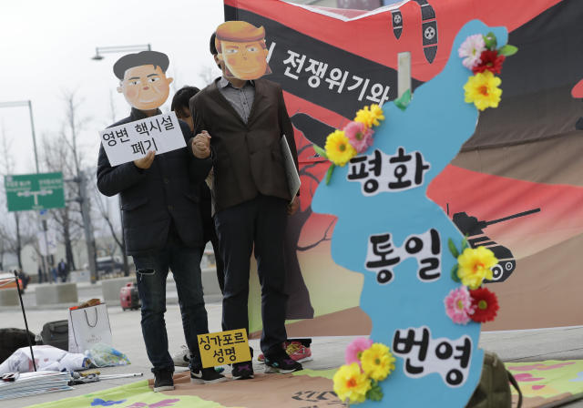 """Protesters wearing masks of U.S. President Donald Trump and North Korean leader Kim Jong Un stand near the map of Korean Peninsula during a rally demanding the denuclearization of the Korean Peninsula and peace treaty near the U.S. embassy in Seoul, South Korea, Thursday, March 21, 2019. The Korean Peninsula remains in a technical state of war because the 1950-53 Korean War ended with an armistice, not a peace treaty. More than 20 protesters participated at a rally and also demanding the end the Korean War and to stop the sanction on North Korea. The letters read """"Peace and Unification."""" (AP Photo/Lee Jin-man)"""