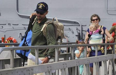 Eric and Charlotte Kaufman and their two daughters, 3-year-old Cora and 1-year-old Lyra, disembark the USS Vandegrift in San Diego