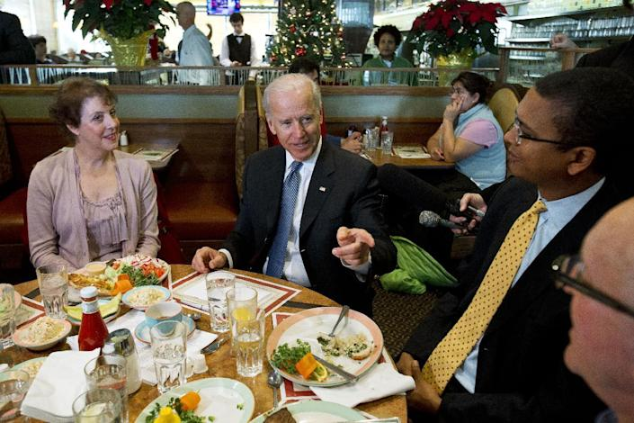 Vice President Joe Biden speaks to the media after eating lunch with middle class tax-payers including, from left, Anne Marie Munos of Falls Church, Va., Mossi Tull, of Washington, and David Waugh, of Bethesda, Md., Friday, Dec. 7, 2012, at the Metro 29 diner in Arlington, Va. (AP Photo/Jacquelyn Martin)