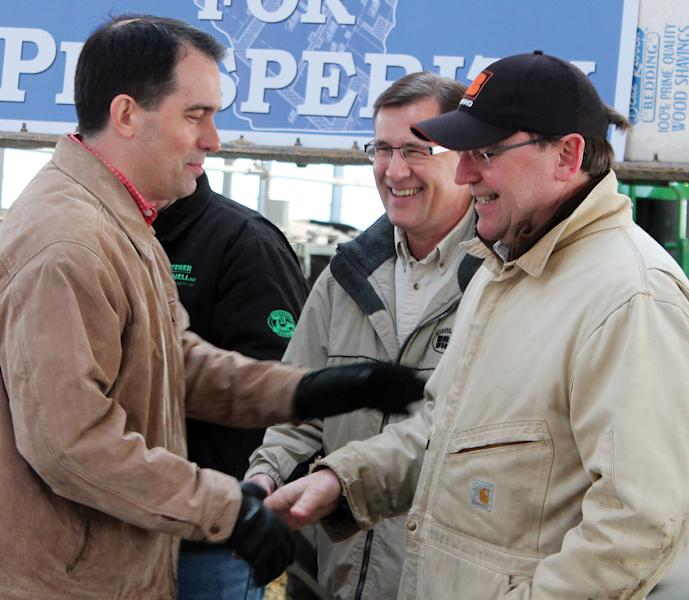 FILE - In this March 24, 2014 file photo Wisconsin Gov. Scott Walker shakes hands with Sen. Tom Tiffany, R-Hazelhurst, before signing his half-billion dollar property and income tax bill at Horsens Homestead Farms in Cecil, Wis. With the two-year legislative session wrapping up Tuesday, April 2, 2014 the campaign season is now heating up with Walker's re-election bid topping the ticket as the premiere statewide race. (AP Photo/The Shawano Leader, Lee Pulaski, File)