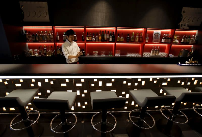 Waiter works in a bar at First Cabin hotel, which was converted from an old office building, in Tokyo