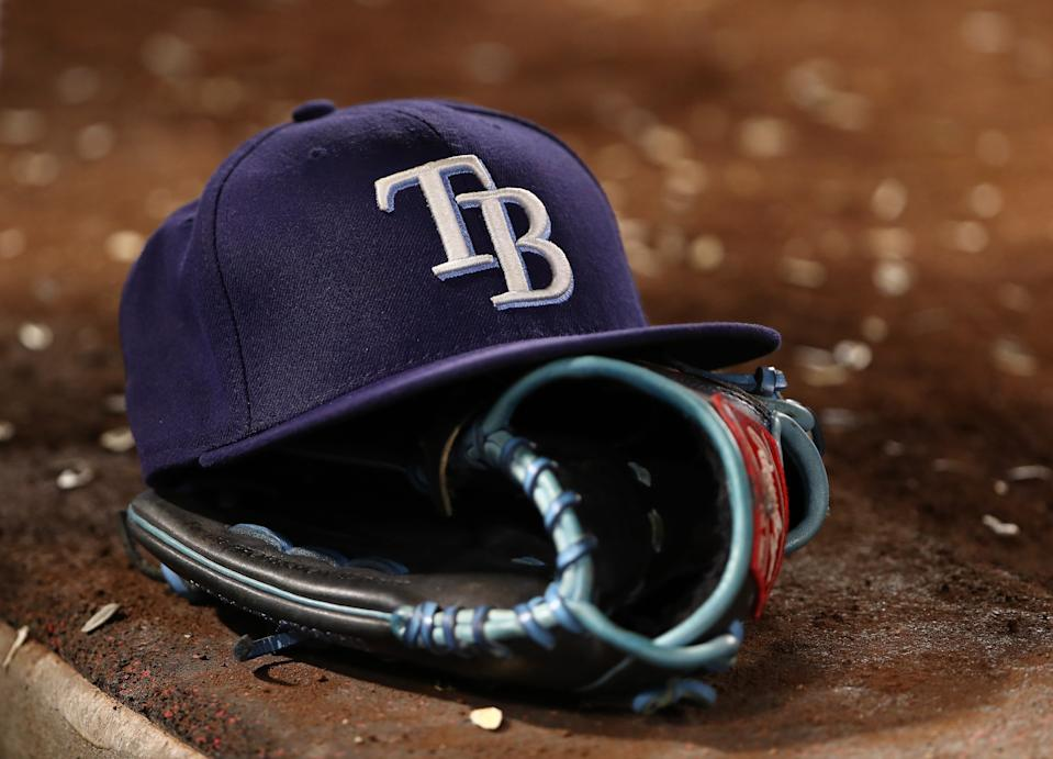 A detailed view of a Tampa Bay Rays hat and catching glove is seen on a dugout step during the sixth inning of the MLB game between the Tampa Bay Rays and the Los Angeles Angels at Angel Stadium of Anaheim on Sept. 14, 2019 in Anaheim, California.