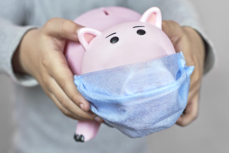 A little boy holding a piggy bank in face mask. Symbol of poor home budget. Personal Budgeting during the Coronavirus Pandemic. COVID-19 hurting family budget, savings and funds