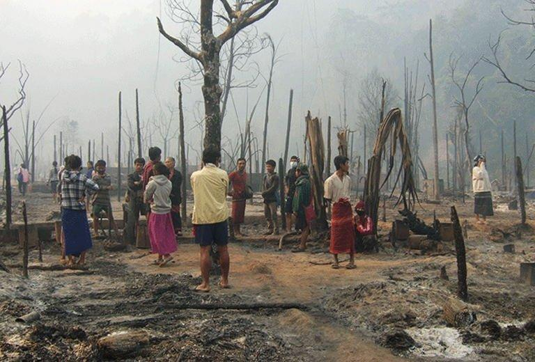 Picture provided by the Thai government shows people standing amid the ruins of burnt homes after a fire swept through the Mae Surin refugee camp in Mae Hong Son province, northern Thailand on March 23, 2013. Thai rescue workers picked through the ashes of hundreds of shelters for Myanmar refugees Saturday after a ferocious blaze swept through the camp in northern Thailand killing 35 people