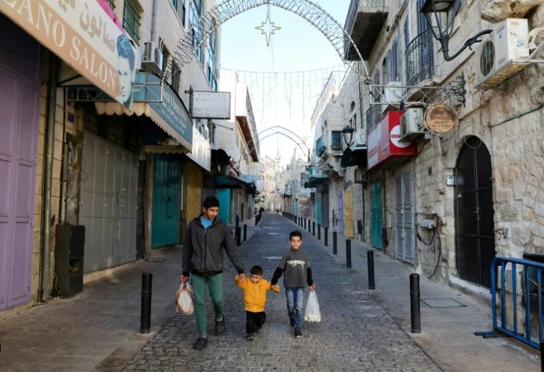 Children walk by shuttered shops in a street decorated ahead of Christmas in Bethlehem in the occupied West Bank amid the novel coronavirus pandemic crisis