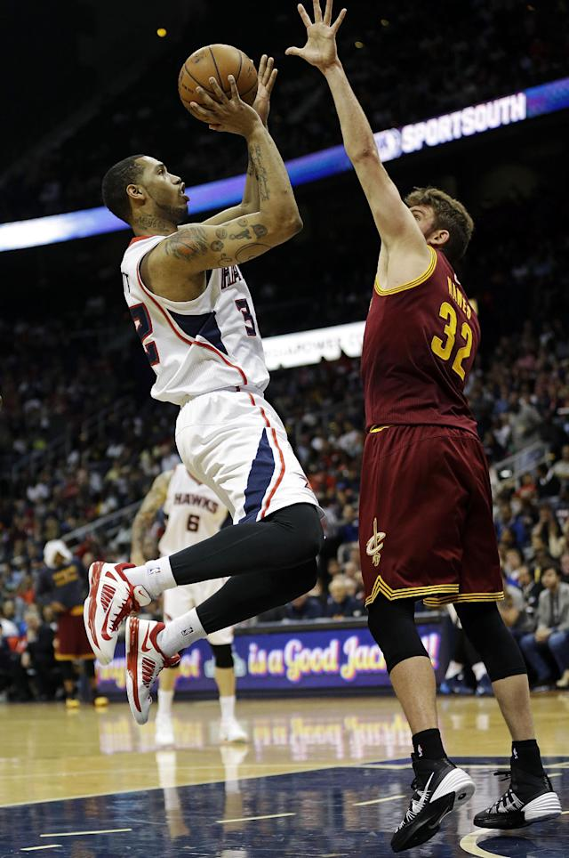 Atlanta Hawks' Mike Scott, left, puts up a shot against Cleveland Cavaliers' Spencer Hawes in the second quarter of an NBA basketball game, Friday, April 4, 2014, in Atlanta. The Hawks beat the Cavaliers 117-98. (AP Photo/David Goldman)