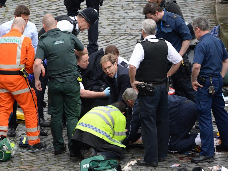 Conservative MP Tobias Ellwood (centre) helps emergency services attend to a police officer outside the Palace of Westminster: PA