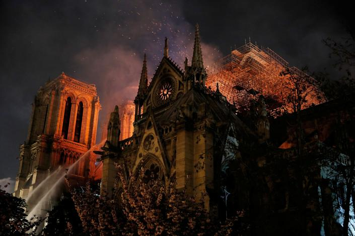 Sparks fill the air as Paris Fire brigade members spray water to extinguish flames as the Notre Dame Cathedral burns in Paris, France, April 15, 2019.   (Photo: Philippe Wojazer/Reuters)