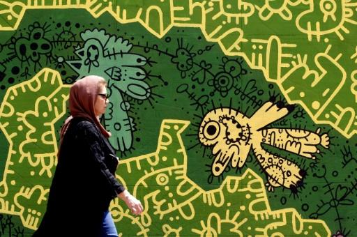A woman walks in front of a mural in the Iranian capital Tehran on August 6, 2018