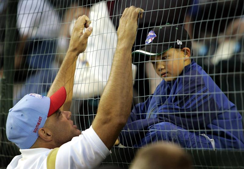 Former major leaguer Dante Bichette, left, talks with his son Bo Bichette, 7, in the stands before coaching his older son Dante Bichette Jr.'s little league team representing Maitland, Fla., against Davenport, Iowa at the Little League World Series Friday, Aug. 19, 2005.