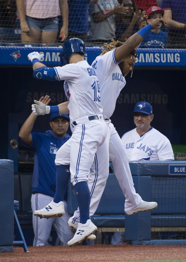 Toronto Blue Jays designated hitter Randal Grichuk, left, celebrates with Blue Jays third baseman Vladimir Guerrero Jr. (27) after hitting a solo home run against the Texas Rangers during the second inning of a baseball game, Tuesday Aug. 13, 2019 in Toronto. (Nathan Denette/The Canadian Press via AP)