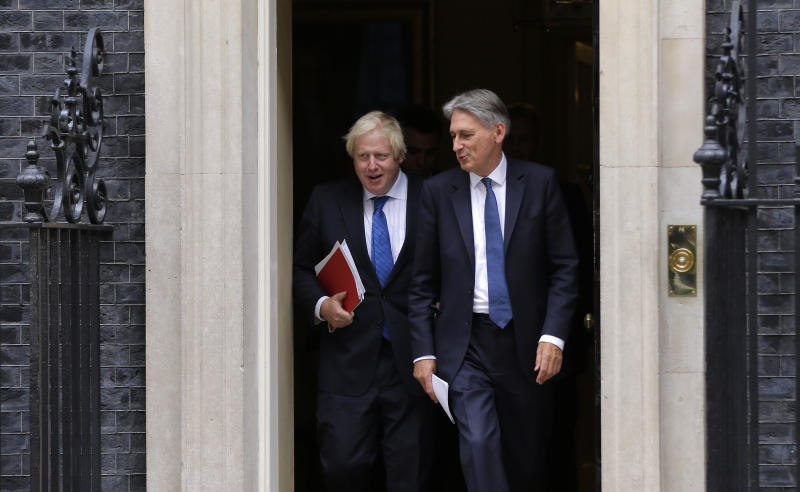 Britain Chancellor of the Exchequer Philip Hammond, right, departs with the Foreign Secretary Boris Johnson after a Cabinet meeting at 10 Downing Street in London, Thursday, Sept. 21, 2017. Britain's Prime Minister Theresa May will give a speech on Britain ongoing negotiations about leaving the EU in Florence, Italy on Friday, and she will brief the cabinet on its contents Thursday. (AP Photo/Alastair Grant)