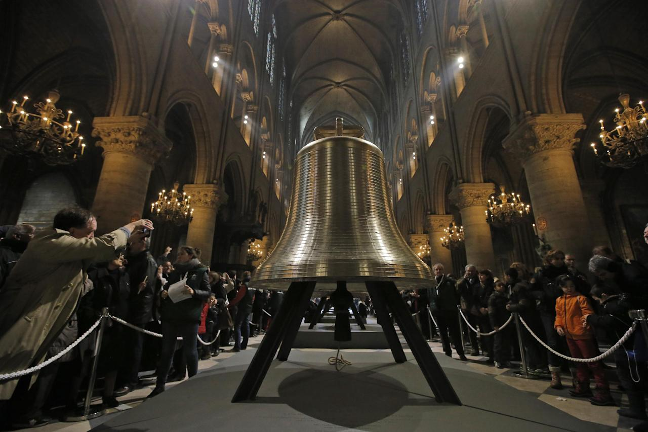 A man takes a photo of one of the nine new bronze bells lined in Notre Dame cathedral during a ceremony of blessing by Paris Archbishop Andre Vingt-Trois in Paris, Saturday, Feb. 2, 2013. Nine enormous new bronze bells have made their way at Notre Dame Cathedral, helping the medieval edifice to rediscover its historical harmony. (AP Photo/Francois Mori)