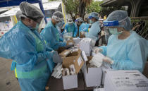 Health workers prepare equipments for nasal swab tests for workers in a local entertainment venue area where a new cluster of COVID-19 infections were found in Bangkok, Thailand, Thursday, April 8, 2021. Thailand has confirmed its first local cases of the coronavirus variant first detected in the U.K., raising the likelihood that it is facing a new wave of the pandemic, a senior doctor said Wednesday. (AP Photo/Sakchai Lalit)