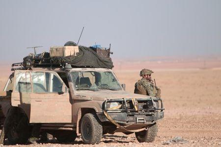 A U.S. fighter stands near a military vehicle, north of Raqqa city