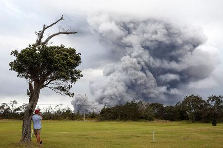A man watches as ash erupts from the Halemaumau crater near the community of Volcano during ongoing eruptions of the Kilauea Volcano in Hawaii, U.S., May 15, 2018.  REUTERS/Terray Sylvester