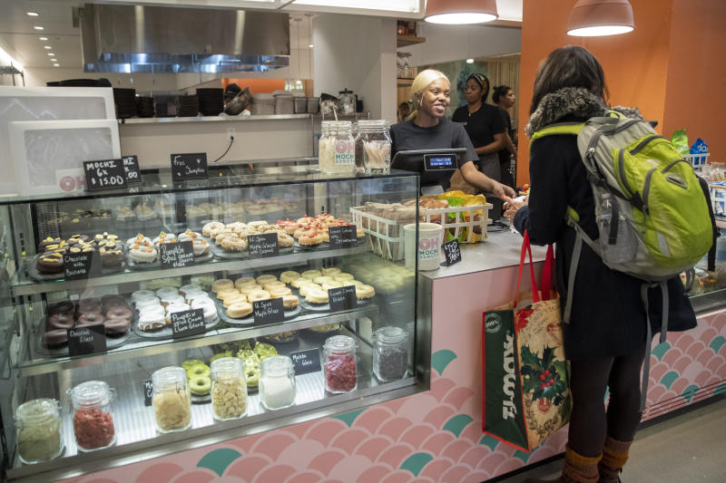 In this Tuesday, Nov. 26, 2019, photo shows a customer service representative waits on a customer Oh Mochi! donut shop at the Nordstrom NYC Flagship in New York. (AP Photo/Mary Altaffer)