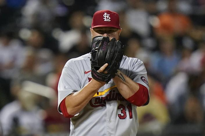 St. Louis Cardinals starting pitcher Jon Lester peers from behind his glove.