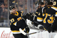 Boston Bruins' Patrice Bergeron is congratulated at the bench after scoring against the Arizona Coyotes during the second period of an NHL hockey game Saturday, Feb. 8, 2020, in Boston. (AP Photo/Winslow Townson)
