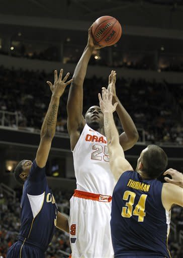 Syracuse forward Rakeem Christmas (25) drives to the basket against California guard Tyrone Wallace (3) and forward Robert Thurman (34) during the first half of a third-round game in the NCAA college basketball tournament Saturday, March 23, 2013, in San Jose, Calif. (AP Photo/Tony Avelar)