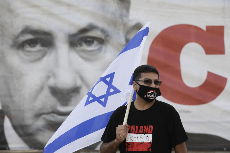 A man holds Israeli flag during a rally against Israel plans to annex parts of the West Bank, in Tel Aviv, Israel, Saturday, June 6, 2020. In the back is a photo os Israeli Prime Minister Benjamin Netanyahu. (AP Photo/Sebastian Scheiner)